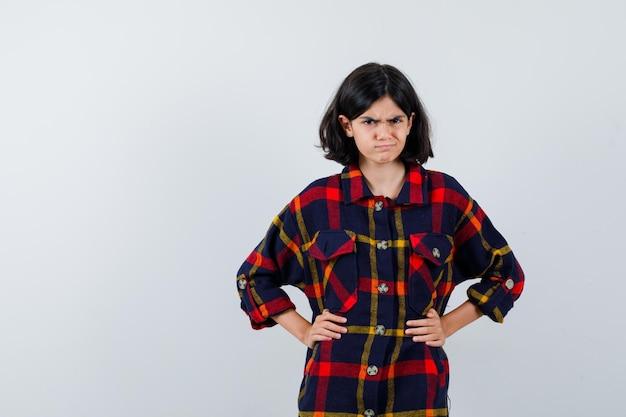 Młoda dziewczyna w kraciastej koszuli trzymając się za ręce w talii i patrząc zły, widok z przodu.