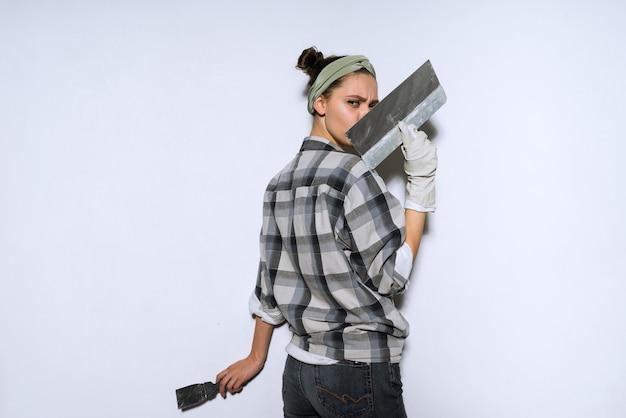 Młoda dziewczyna w kraciastej koszuli wyściela i koloruje ściany w swoim nowym mieszkaniu, remonty