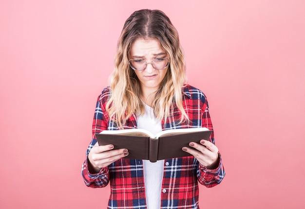 Młoda dziewczyna w kraciastej koszuli z niezrozumieniem patrzy na podręcznik, próbując zdać egzamin na uniwersytecie