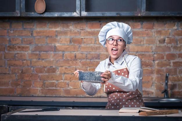 Młoda dziewczyna w kucharzie ubrania z ciasta w ręce