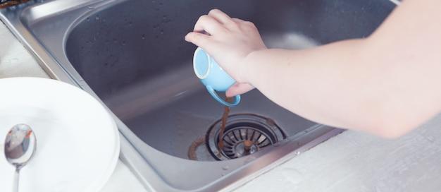 Młoda dziewczyna w kuchni myje naczynia