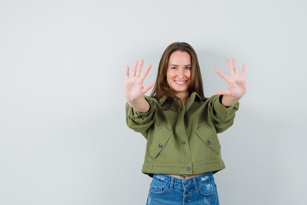Młoda dziewczyna w kurtce, spodenki pokazujące dziesięć palców i wesoło wyglądające, widok z przodu.