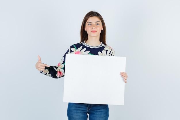 Młoda dziewczyna w kwiecista bluzka, dżinsy pokazujące papierowy plakat i patrząc pewnie, widok z przodu.