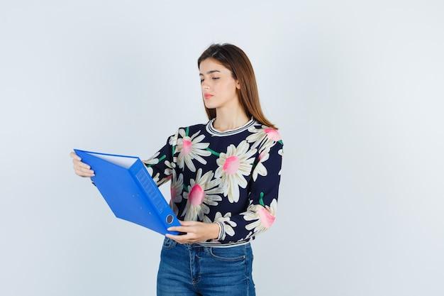 Młoda dziewczyna w kwiecistej bluzce, dżinsach patrząc na folder i patrząc zamyślony, widok z przodu.