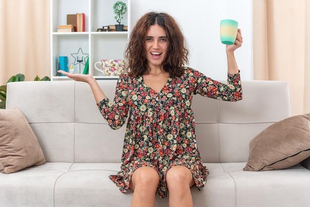 Młoda dziewczyna w kwiecistej sukience trzymająca filiżankę herbaty, uśmiechając się radośnie, prezentując ramieniem dłoni, siedząc na kanapie w jasnym salonie
