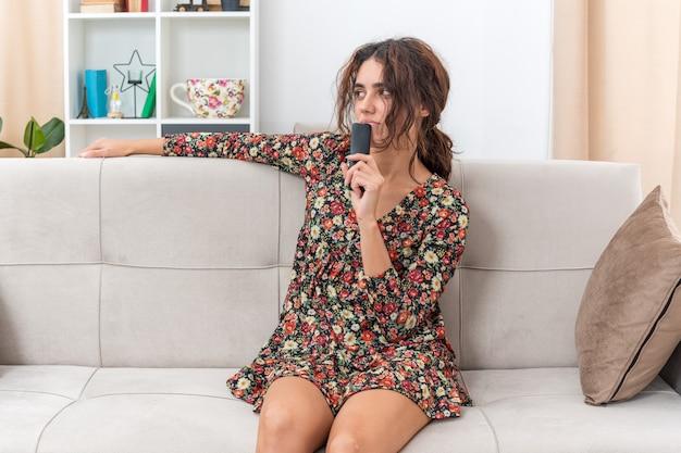 Młoda dziewczyna w kwiecistej sukience trzymająca pilota od telewizora patrząca na bok zdziwiona siedząca na kanapie w jasnym salonie
