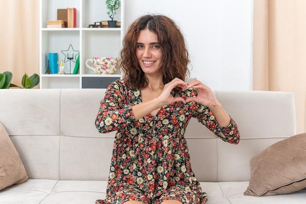 Młoda dziewczyna w kwiecistej sukience, uśmiechnięta radośnie, wykonująca gest serca palcami siedzącymi na kanapie w jasnym salonie living