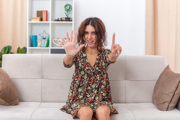 Młoda dziewczyna w kwiecistej sukience wygląda szczęśliwie i pozytywnie pokazując cyfrę pięć i uśmiechający się palec wskazujący, siedząc na kanapie w jasnym salonie