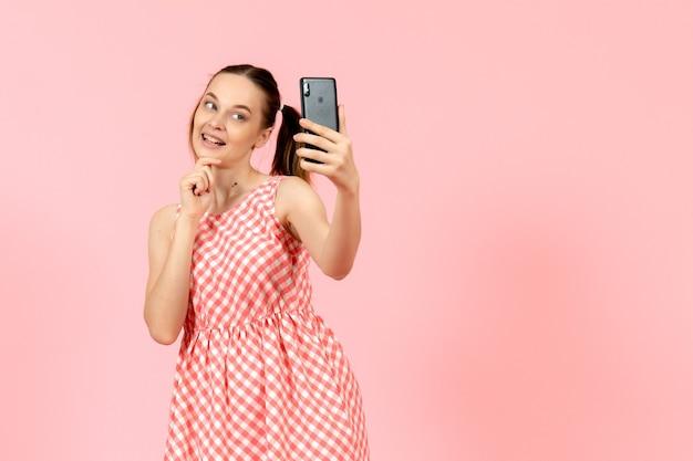 Młoda dziewczyna w ładny jasny strój przy selfie na różowo