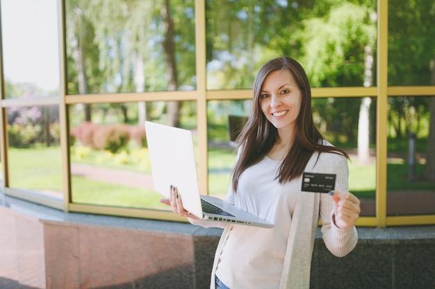 Młoda dziewczyna w lekkim ubraniu posiadającym kartę kredytową. kobieta pracująca na nowoczesnym laptopie w pobliżu lustrzanego budynku z odbiciem drzewa na ulicy na zewnątrz. biuro mobilne. koncepcja biznesowa niezależnego.