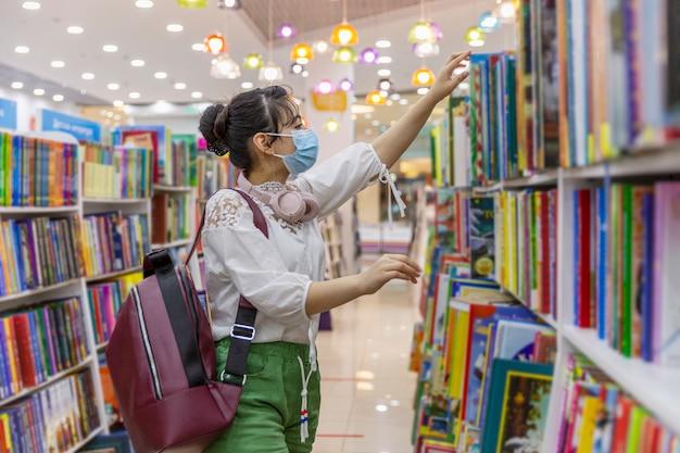 Młoda dziewczyna w masce medycznej wybiera książkę w księgarni. wiedza i edukacja. środki ostrożności podczas pandemii koronawirusa.