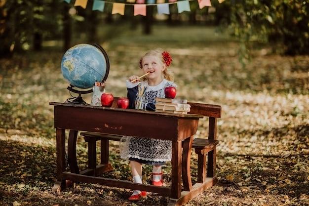 Młoda dziewczyna w mundurek szkolny siedzi przy starym drewnianym biurkiem z kulą ziemską
