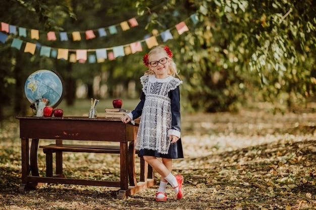 Młoda dziewczyna w mundurku szkolnym i szkłach pozuje blisko starego drewnianego biurka z kulą ziemską