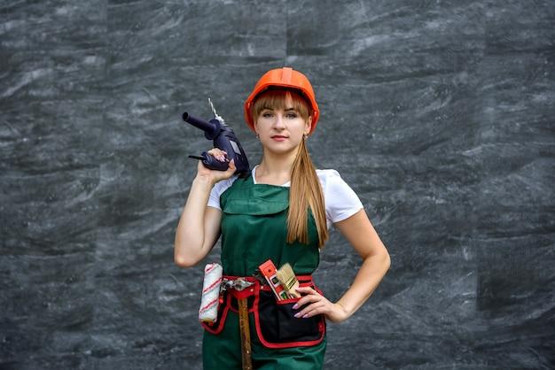 Młoda dziewczyna w mundurze i kasku dokonuje napraw przy pomocy wiertarki.