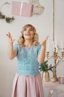 Młoda dziewczyna w niebieskiej bluzce i różowej spódnicy rzuca prezent i śmieje się. na nowy rok w pokoju studio z wystrojem w pastelowych tonacjach