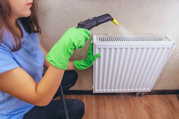 Młoda dziewczyna w niebieskim mundurze roboczym z myjką parową szczotkującą baterię domową