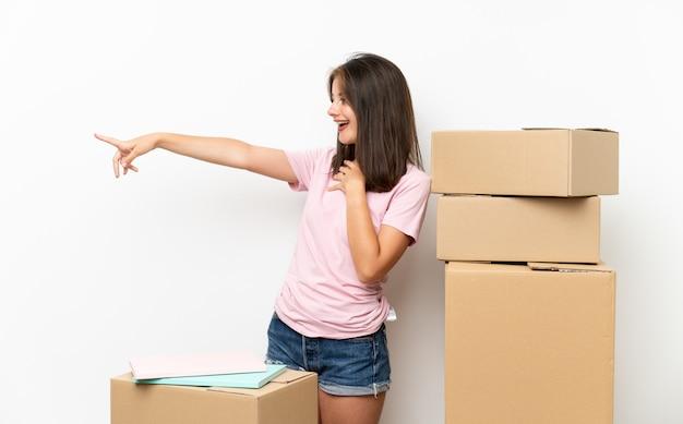 Młoda dziewczyna w nowym domu wśród pól, wskazując palcem na bok