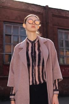 Młoda dziewczyna w odpiętym żakiecie cieszy się słońce. lustrzane okulary przeciwsłoneczne z ulicą odbijającą się w nim.