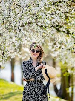 Młoda dziewczyna w okularach przeciwsłonecznych i kapeluszu pobycie blisko kwiatonośnego drzewa
