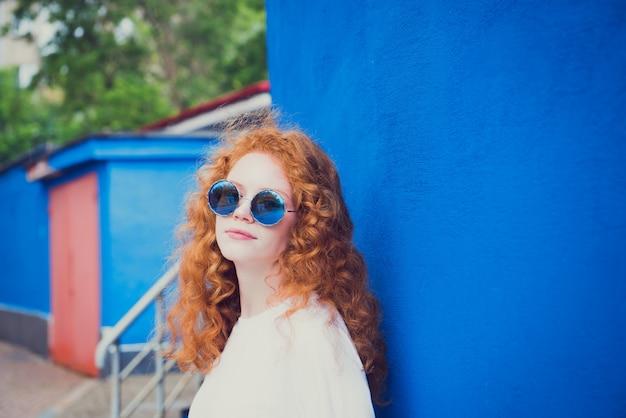 Młoda dziewczyna w okularach przeciwsłonecznych na niebieskim tle