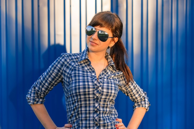 Młoda dziewczyna w okularach przeciwsłonecznych w koszula na błękicie