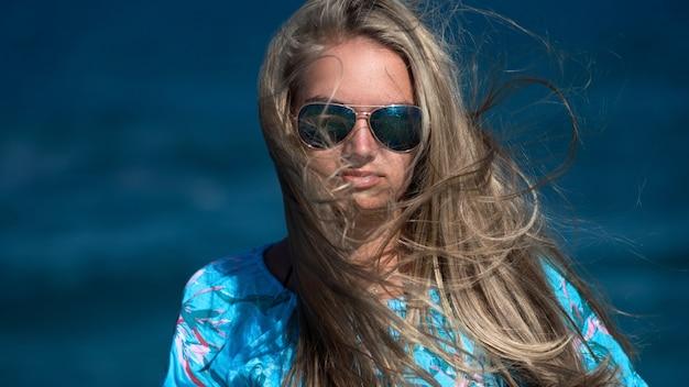 Młoda dziewczyna w okularach przeciwsłonecznych z długie włosy na a błękitny morze.