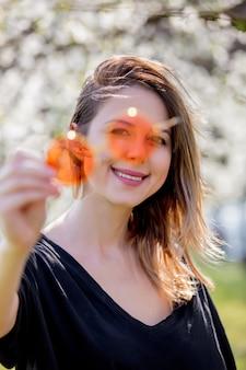 Młoda dziewczyna w okularach przeciwsłonecznych zostaje blisko kwitnącego drzewa