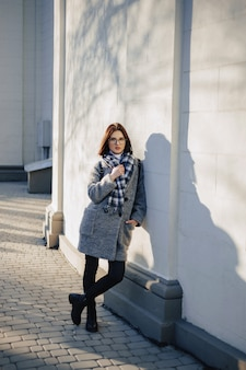 Młoda dziewczyna w okularach w płaszczu spaceru w słoneczny dzień