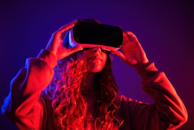 Młoda dziewczyna w okularach wirtualnej rzeczywistości z niebieskim i czerwonym oświetleniem w pokoju. rozrywka w domu