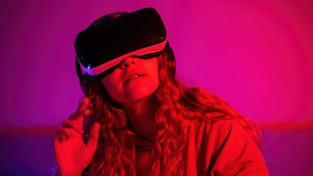 Młoda dziewczyna w okularach wirtualnej rzeczywistości z niebieskim i czerwonym oświetleniem w pokoju z podniesioną ręką. rozrywka w domu