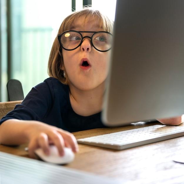 Młoda dziewczyna w okularach zszokowana korzystaniem z komputera