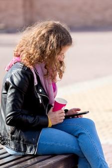 Młoda dziewczyna w parku na ławce picia kawy i patrząc na smartphone_