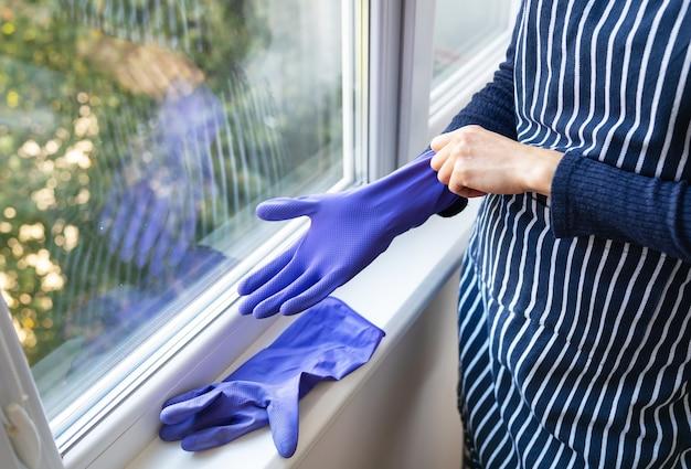 Młoda dziewczyna w pasiastym fartuchu zakłada na ręce fioletowe rękawiczki. przygotowanie do mycia okien w mieszkaniu lub domu. koncepcja czyszczenia i czyszczenia.