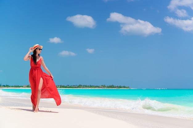 Młoda dziewczyna w pięknej czerwonej sukience nad brzegiem morza