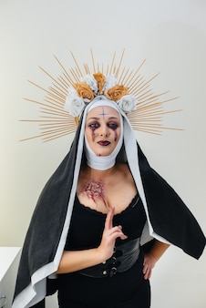 Młoda dziewczyna w pięknym świątecznym makijażu i przerażającym stroju zakonnicy na halloween. happy halloween koncepcja.