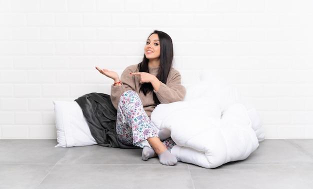 Młoda dziewczyna w piżamie w pomieszczeniu gospodarstwa wyobraźni puste miejsce na dłoni