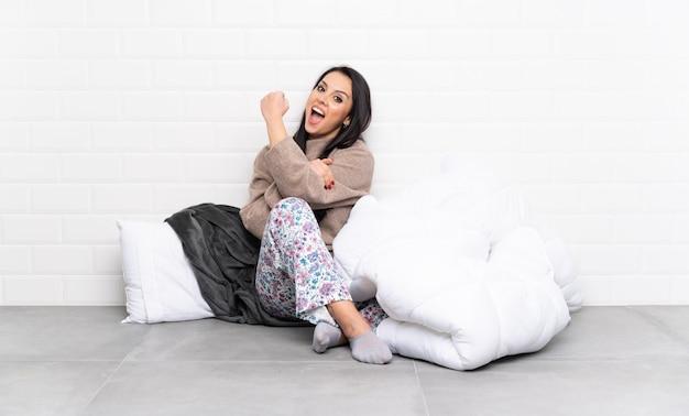 Młoda dziewczyna w piżamie w pomieszczeniu robi silny gest
