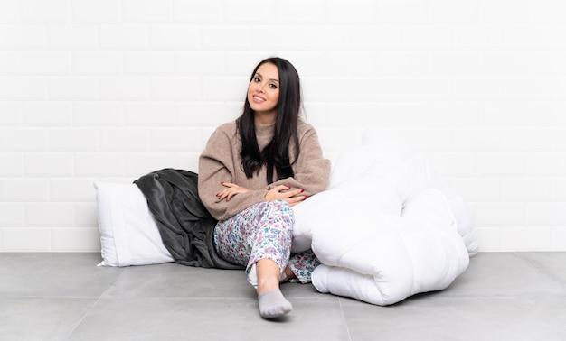 Młoda dziewczyna w piżamie w pomieszczeniu z rękami skrzyżowanymi i czekamy