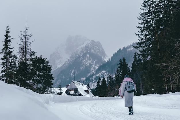 Młoda dziewczyna w płaszczu iz plecakiem w zimie patrzy na góry. turystyka wakacyjna w ośrodku narciarskim. wędrówki w pięknym krajobrazie.