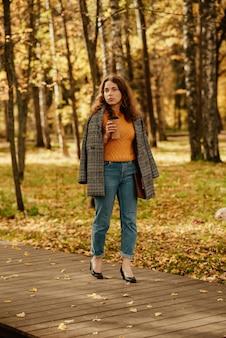 Młoda dziewczyna w płaszczu spaceruje po jesiennym parku