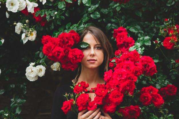 Młoda dziewczyna w pobliżu krzewu czerwonych i białych róż