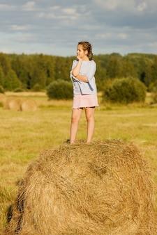 Młoda dziewczyna w polu lato. na rolce siana.