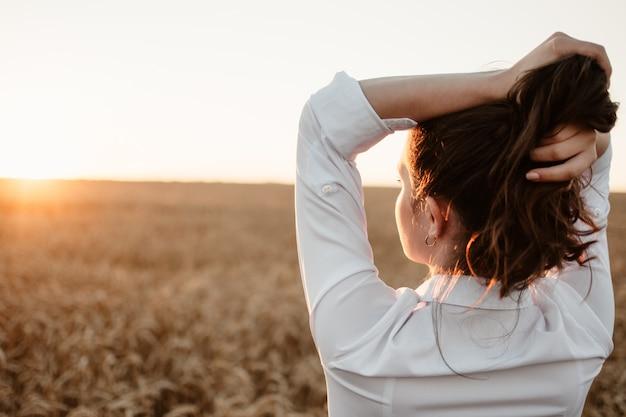 Młoda dziewczyna w polu pszenicy o zachodzie słońca. powolne życie, koncepcja zdrowia psychicznego