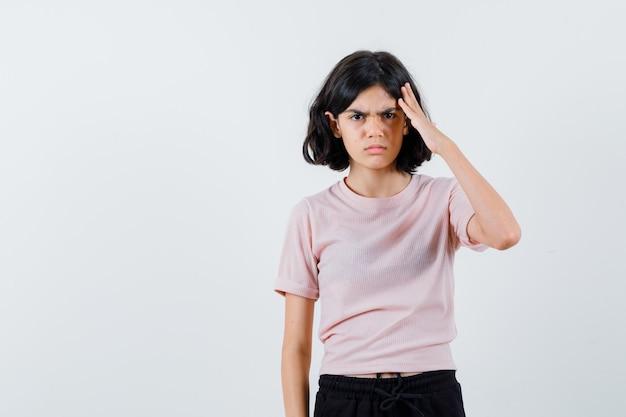 Młoda dziewczyna w różowej koszulce i czarnych spodniach kładzie rękę na głowie i szuka wściekłości