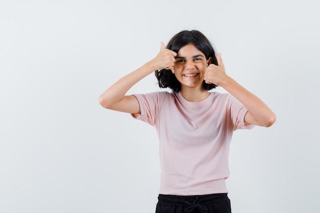 Młoda dziewczyna w różowej koszulce i czarnych spodniach pokazuje kciuki obiema rękami i wygląda na szczęśliwą