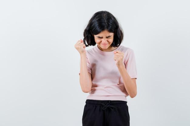 Młoda dziewczyna w różowej koszulce i czarnych spodniach pokazuje pozę zwycięzcy i wygląda na szczęśliwego