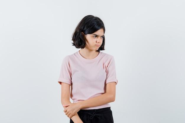 Młoda dziewczyna w różowej koszulce i czarnych spodniach stoi prosto, odwraca wzrok i pozuje do kamery i wygląda ponuro