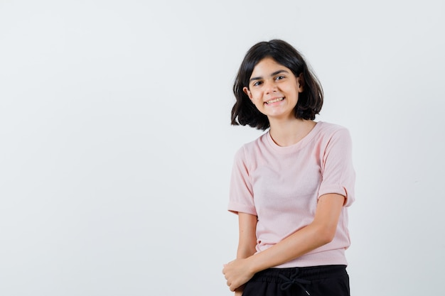Młoda dziewczyna w różowej koszulce i czarnych spodniach, stojąc prosto i pozuje do kamery i patrząc szczęśliwy