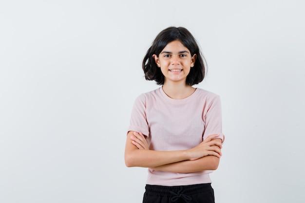 Młoda dziewczyna w różowej koszulce i czarnych spodniach, stojąc z rękami skrzyżowanymi, uśmiechając się i patrząc na szczęśliwego