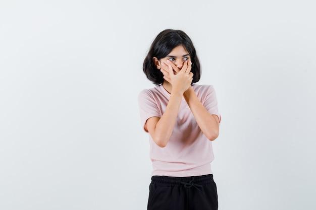 Młoda dziewczyna w różowej koszulce i czarnych spodniach zakrywających usta obiema rękami i wyglądająca uroczo